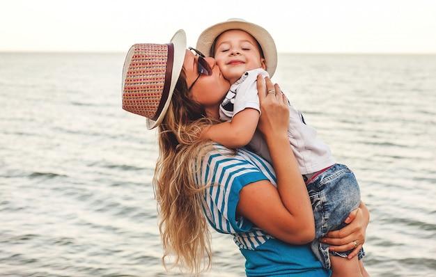 Synek w ramionach, przytula mamę nad brzegiem morza