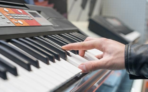 Syntezator z klawiaturą fortepianową z ręką grającą na nim