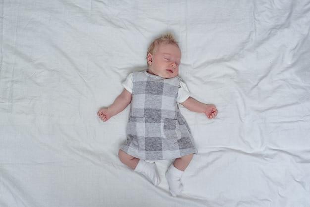 Sypialna nowonarodzona dziewczyna w sukni na białym prześcieradle. widok z góry. miejsce na tekst