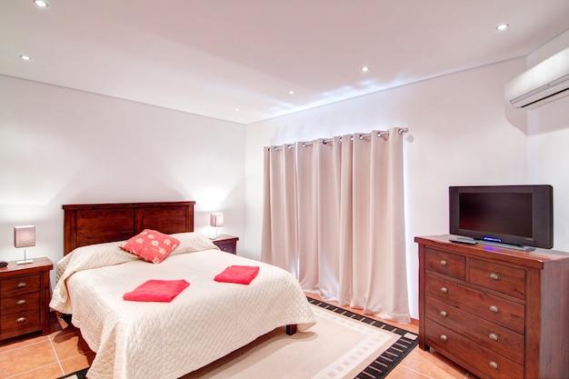 Sypialnia dla dwóch osób z telewizorem. w dekoracji.
