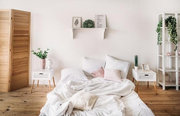 Sypialnia jest jasna i wygodna z dużym łóżkiem i białymi drewnianymi meblami oraz kwiatowo-zielonym wystrojem.