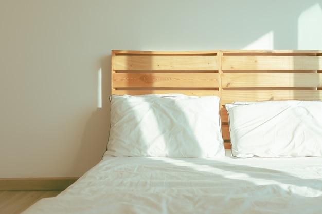 Sypialnia na poddaszu z białym łóżkiem w łagodnym słońcu zimowego poranka.
