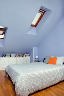 Sypialnia na poddaszu z podwójnym łóżkiem i komodą z książkami