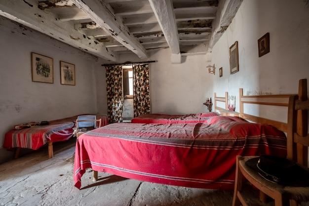 Sypialnia starego domu z wieloma łóżkami