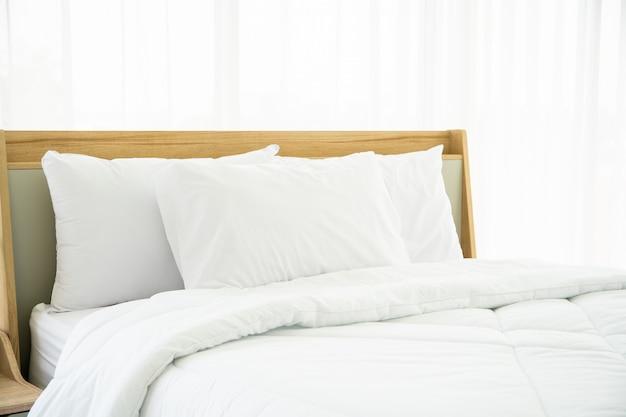 Sypialnia urządzona w minimalistycznym stylu, fotografia białych poduszek i drewniane łóżko w sypialni z naturalnym światłem z okna.