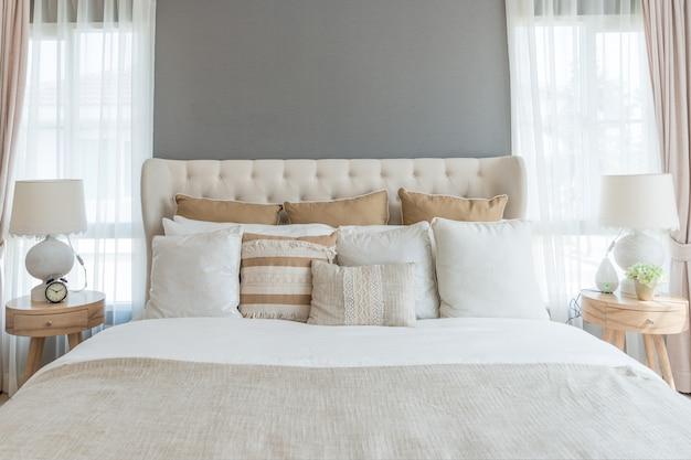 Sypialnia w delikatnych jasnych kolorach. duże wygodne podwójne łóżko w eleganckiej klasycznej sypialni w domu.
