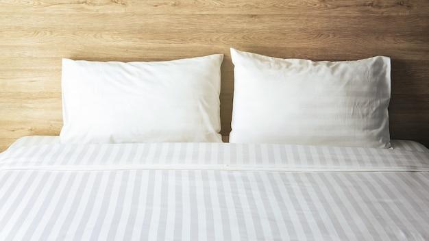 Sypialnia z białym łóżkiem, białe dwie poduszki, biała kołdra na łóżku z drewnianym zagłówkiem i światłem słonecznym