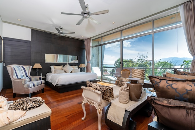 Sypialnia z drzwiami ze szkła, wentylatorem sufitowym i drewnianymi podłogami w willi przy basenie, domu, domu, mieszkania i mieszkania