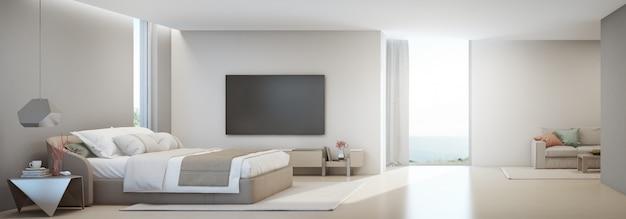 Sypialnia z widokiem na morze i salon luksusowego letniego domu na plaży z podwójnym łóżkiem w pobliżu drewnianej szafki.