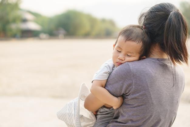 Sypialny azjatycki dziecko trzyma jego matką