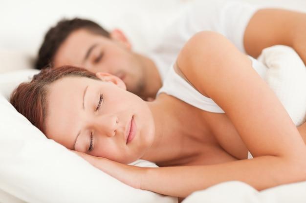 Sypialny pary lying on the beach w ich łóżku