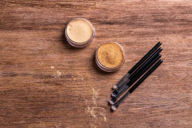 Sypki puder mineralny w kompakcie do twarzy oraz pędzle do pudru i wizażu na drewnianym tle. kosmetyki ekologiczne i organiczne.