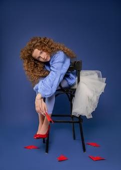 Syrenka nastolatka. strzał studio. kobieta, modelka w papierowej wodzie siedzi na krześle w pięknej sukni mody wśród czerwonych ryb origami.