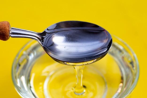 Syrop cukrowy w szklanej misce na żółtym tle.