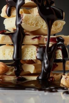 Syrop czekoladowy wylewany na pojedyncze kawałki białej czekolady