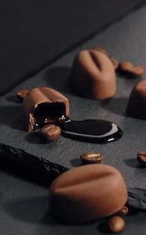 Syrop kawowy wyciekł z łamanej czekolady kawowej na kamiennym talerzu