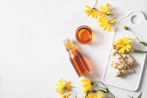 Syrop z topinamburu w misce z kwiatami i korzeniem