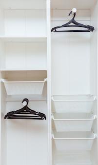 System przechowywania: białe kosze i wieszaki na ubrania