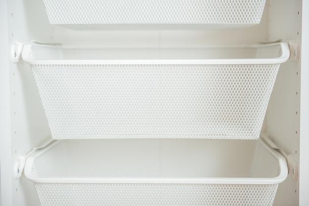 System przechowywania: białe puste metalowe kosze na ubrania w garderobie