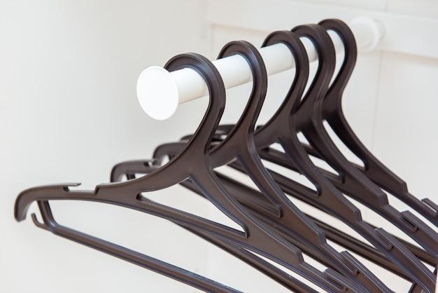 System przechowywania: czarne wieszaki na ubrania wewnątrz białej szafy