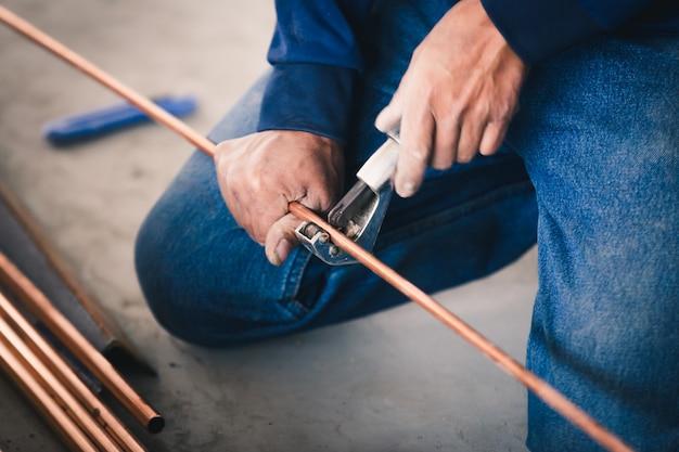 System przemysłu mężczyzn pracownik cięcia wspólnego z narzędziem z rury miedzianej klimatyzatora