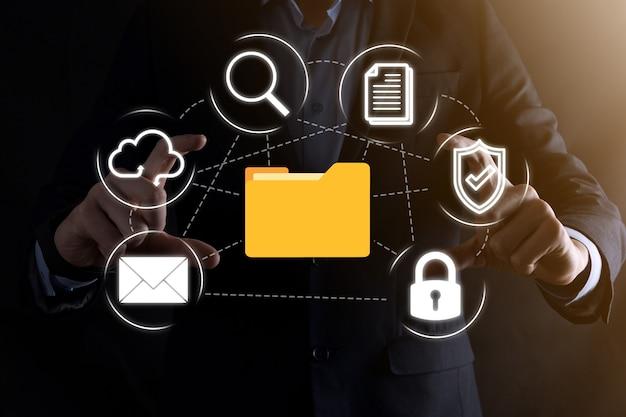 System zarządzania dokumentami dms. biznesmen przytrzymaj ikonę folderu i dokumentu. oprogramowanie do archiwizacji, wyszukiwania i zarządzania plikami firmowymi i informacjami. koncepcja technologii internetowej. bezpieczeństwo cyfrowe.