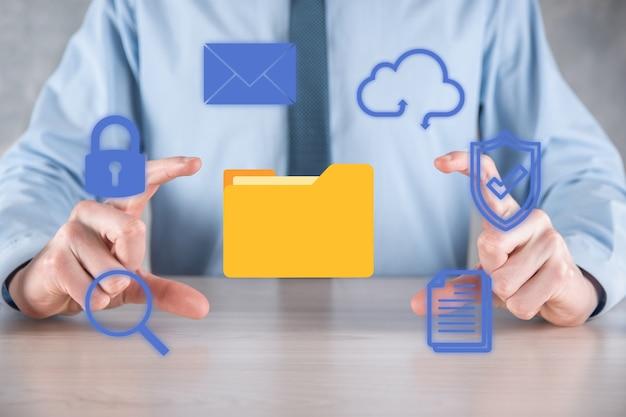 System zarządzania dokumentami dms. biznesmen przytrzymaj ikonę folderu i dokumentu. oprogramowanie do archiwizacji, wyszukiwania i zarządzania plikami i informacjami firmowymi. koncepcja technologii internetowej. bezpieczeństwo cyfrowe