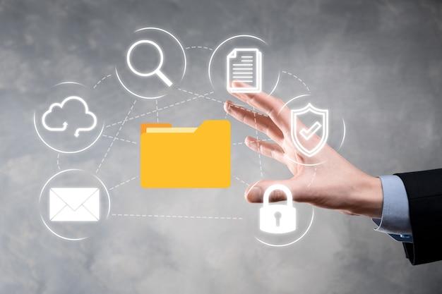 System zarządzania dokumentami dms. biznesmen trzyma ikonę folderu i dokumentu. oprogramowanie do archiwizacji