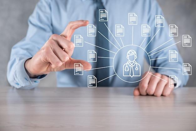System zarządzania dokumentami dms. biznesmen trzyma ikonę lekarza i dokumentu. oprogramowanie do archiwizacji