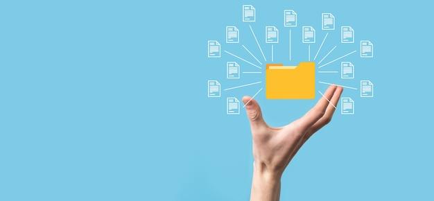 System zarządzania dokumentami (dms). biznesmen trzymać ikonę folderu i dokumentu. oprogramowanie do archiwizacji, wyszukiwania i zarządzania plikami firmowymi i informacjami. koncepcja technologii internetowej. bezpieczeństwo cyfrowe.