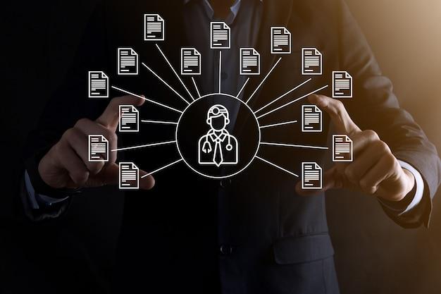 System zarządzania dokumentami dms. biznesmen trzymaj ikonę lekarza i dokumentu. oprogramowanie do archiwizacji, wyszukiwania i zarządzania plikami firmowymi i informacjami. koncepcja technologii internetowej. bezpieczeństwo cyfrowe.