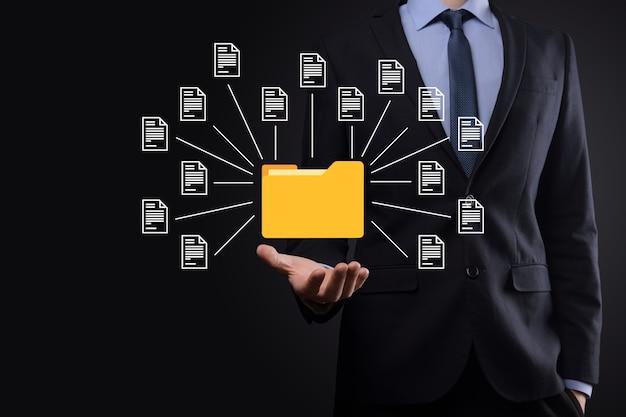 System zarządzania dokumentami dms. businessman przechowuje folder i ikonę dokumentu. oprogramowanie do archiwizacji, wyszukiwania i zarządzania plikami i informacjami firmowymi. koncepcja technologii internetowej. bezpieczeństwo cyfrowe.