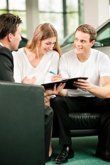 Sytuacja sprzedaży w salonie samochodowym, młoda para podpisuje umowę sprzedaży