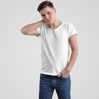 Szablon biała koszulka męska na młodym chłopaku na tle w studio. makiety do prezentacji designu i reklamy w sklepie internetowym. przedni widok.