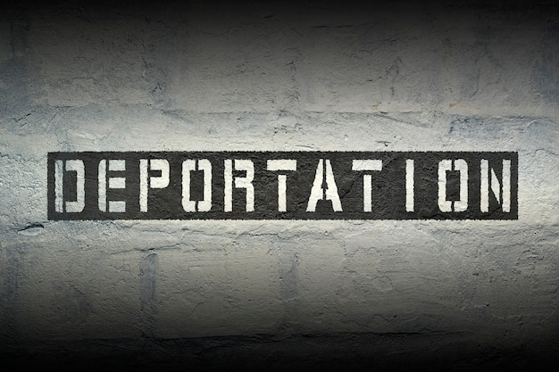 Szablon do deportacji wydrukowany na grunge białej ścianie z cegły