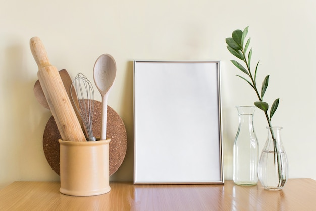 Szablon makiety z dużą srebrną ramą a4, drewnianymi naczyniami kuchennymi i rośliną zamioculcas w szklanym wazonie.