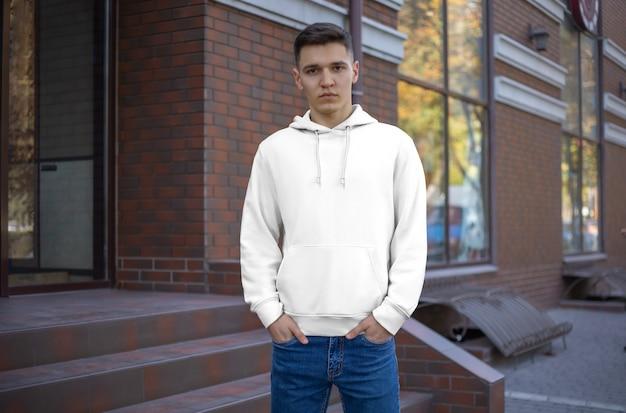 Szablon męska biała bluza z kapturem na faceta, widok z przodu, prezentacja ubrań na ulicy. okapy makiety na tle ceglanego budynku. miejsce na twój wzór i projekt.