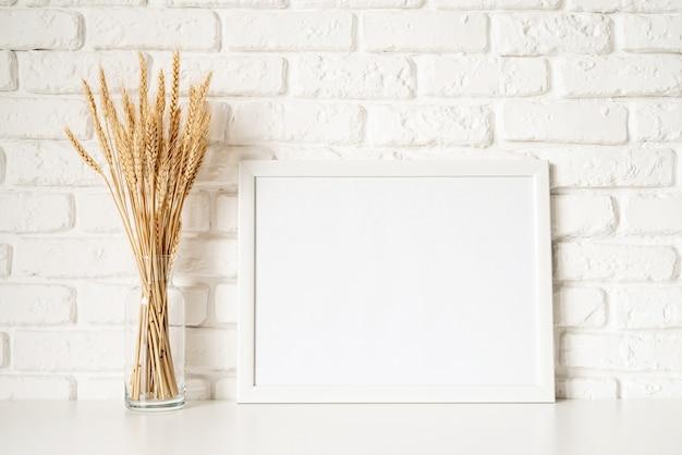 Szablon plakatu makiety z dekoracją pszenicy na tle białej cegły ściany. skopiuj miejsce