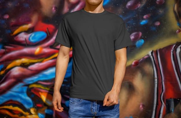 Szablon pustej koszulki na młodym facecie w niebieskich dżinsach na tle ściany z graffiti, widok z przodu. makieta czarnych ubrań do prezentacji designu i reklamy w sklepie internetowym