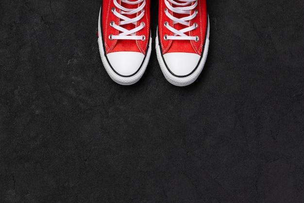 Szablon z letniego obuwia na czarnym tle. płaskie leżały czerwone trampki z widokiem z góry. koncepcja sprzedaży moda zakupy