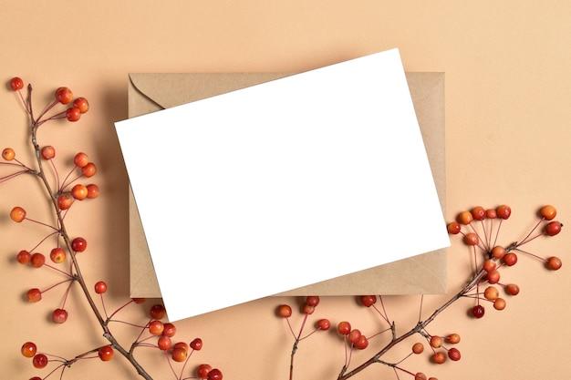 Szablon zaproszenia z kopertą na beżowym tle z jesienną gałęzią jabłoni. romantyczna nuta. układ płaski, widok z góry, miejsce do kopiowania. układ płaski, widok z góry, miejsce do kopiowania.