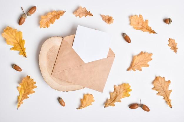 Szablon zaproszenia z kopertą na białym tle z jesiennymi liśćmi dębu i żołędziami. jesienna pocztówka. układ płaski, widok z góry, miejsce do kopiowania.