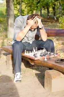 Szachista w rozpaczy siedzi okrakiem na rustykalnej drewnianej ławce z szachownicą przed sobą i głową w dłoniach