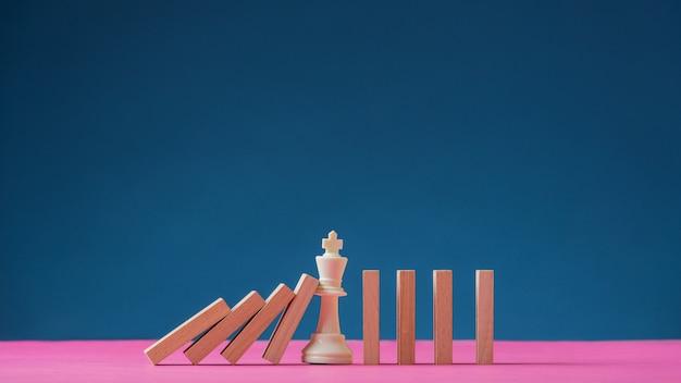 Szachowa figura króla stojąca pośrodku spadających domina