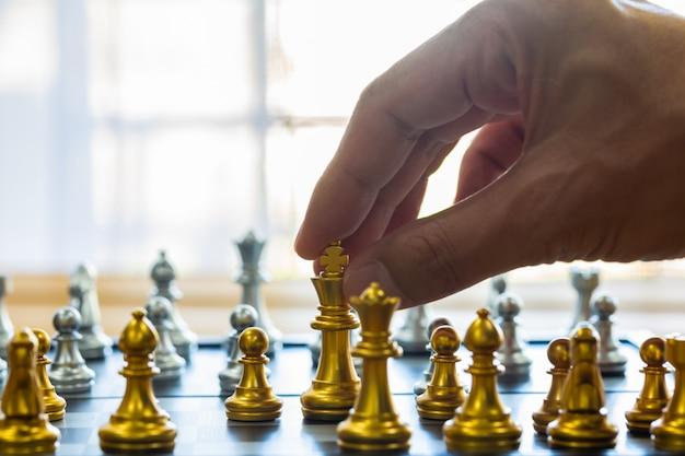 Szachowa gra na szachowej desce za biznesowego mężczyzna tłem.