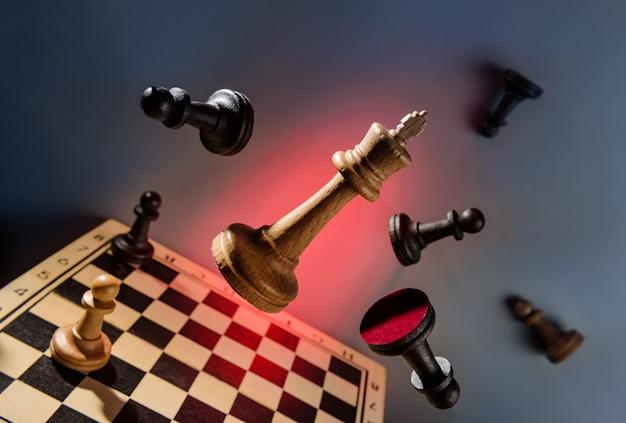 Szachowa królowa przełamuje obronę lewitujących czarnych pionów nad szachownicą pomyślna koncepcja biznesowa
