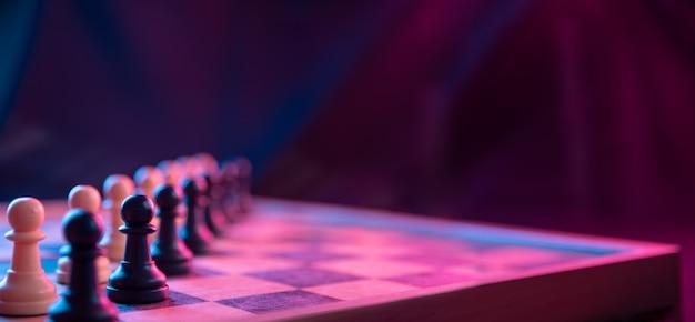 Szachy na szachownicy na ciemnym tle nakręcone w neonowych różowo-niebieskich kolorach.