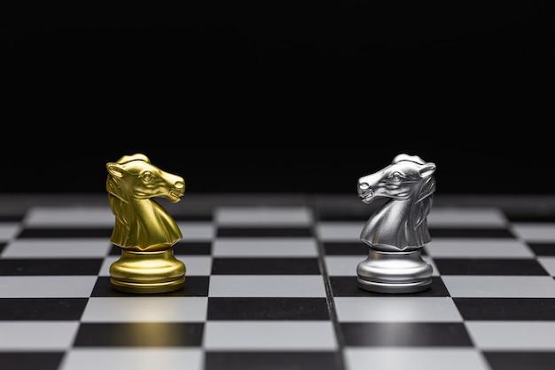 Szachy srebrnych i złotych koni stoją naprzeciw siebie w grze w szachy