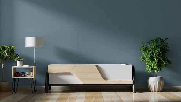 Szafka tv w pustym wnętrzu, ciemna ściana z drewnianą półką, lampa, rośliny i drewno stołowe.