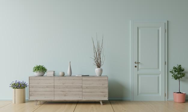 Szafka z rośliną i drzwiami przed białą ścianą.